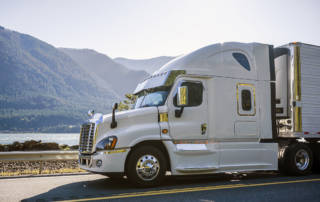 White semi truck driving a refrigerated trailer hauling temperature-controlled freight.